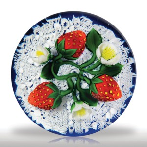 James Kontes strawberries and lace paperweight. Three freckled, ripe, red strawberries and three white strawberry blossoms, each with a bright tuft of yellow stamens at its core, share a twisting vine with four dark green leaves, over a beautifully articulated white lace atop a translucent cobalt blue ground.