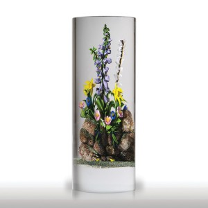 """Randall Grubb """"Garden Wall"""" large glass column sculpture. A remarkable technical achievement and a stunning design, Randall Grubb regales us with both his artistry and his skill. A beautiful tall stalk of purple delphinium, and another of white foxglove, rise high above a cluster of yellow daffodils and small blooms in blue and white, all of them hugging a speckled gray rock wall, as if a favorite slice of someone's garden had been captured for the ages."""