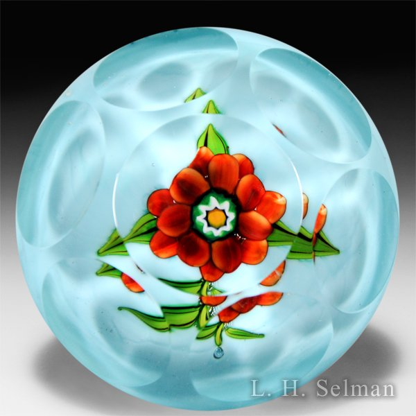 Ronald Hansen red flower on light blue cushion ground faceted glass paperweight. by Ronald Hansen