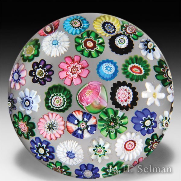 Antique Clichy scattered millefiori with central rose on clear ground glass paperweight. by  Clichy