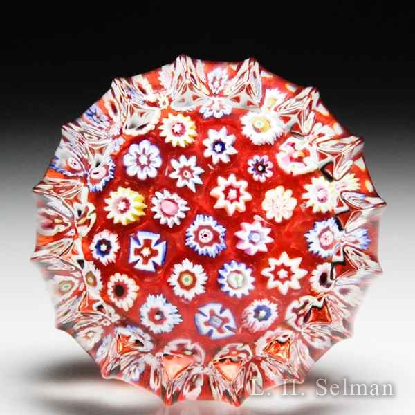 John Deacons (2016) red spaced millefiori miniature fluted paperweight. by John Deacons