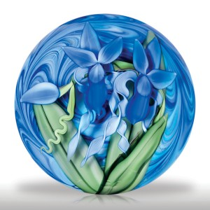 Steven Lundberg Glass Art 2002 two iris compound magnum paperweight, by Justin Lundberg. Two royal blue iris blooms, accompanied by long, thick and bladed leaves as well as pale blue spiraling ribbons of flora and a large blue bud, display against dramatically swirling blues atop a cobalt ground. Edition #2 of a limited edition of 25.