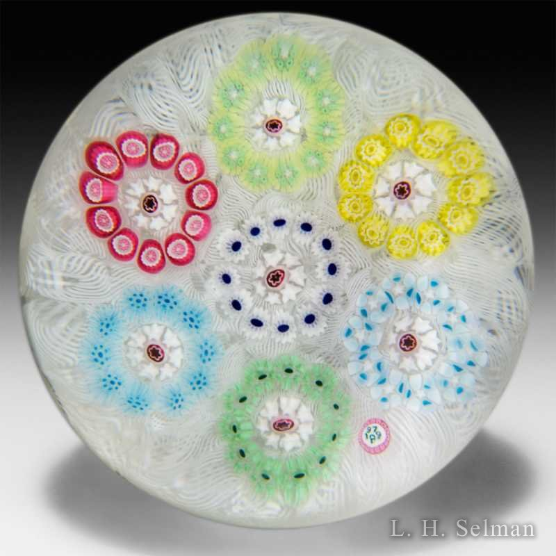 Baccarat 1972 seven millefiori circlets on upset muslin paperweight. by Baccarat Moderns