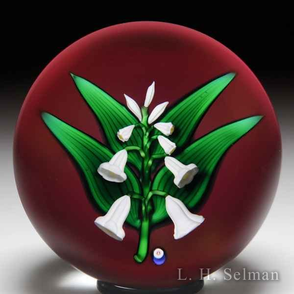Bob Banford lily-of-the-valley on ruby ground glass paperweight. by Bob Banford