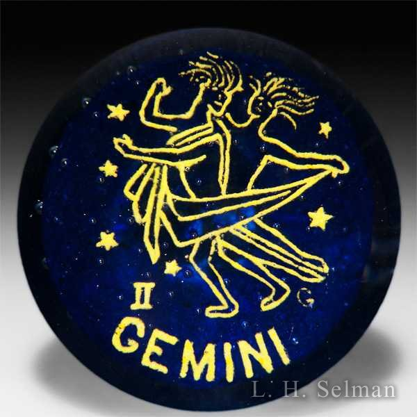 "Gentile Glass ""Gemini"" frit zodiac symbol over bubble studded blue ground glass paperweight. by  Misc Modern"