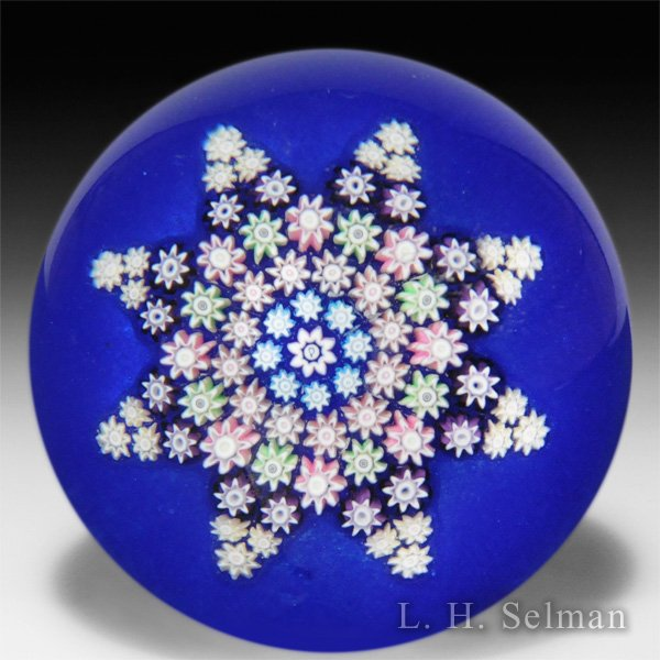 Perthshire Paperweights patterned millefiori star on translucent blue ground glass paperweight. by  Perthshire Paperweights