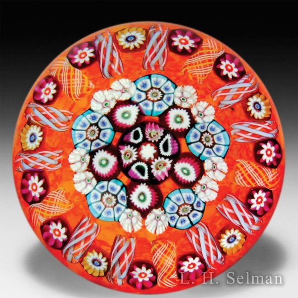 Paul Ysart close concentric millefiori on bright orange ground glass paperweight. by Paul Ysart