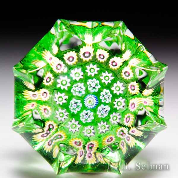 John Deacons (2016) green concentric millefiori miniature star-pressed glass paperweight. by John Deacons