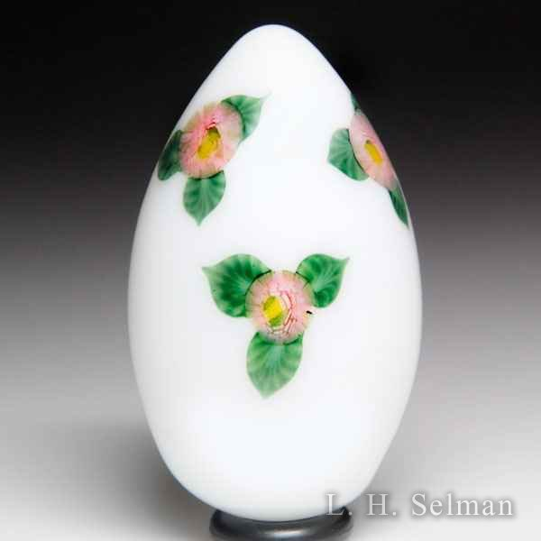 Lundberg Studios pink rose cane on white egg-shaped paperweight, by Daniel Salazar. by Lundberg Studios