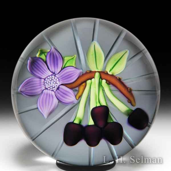 Caithness Glass (1982) 'Cherries' on a branch with a flower glass paperweight, by William Manson. by Caithness  Glass Inc