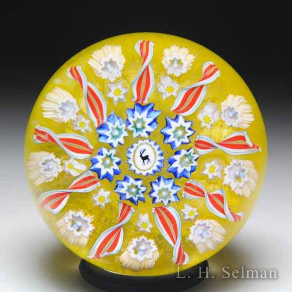 John Deacons (2019) radial twists patterned millefiori miniature glass paperweight. by John Deacons