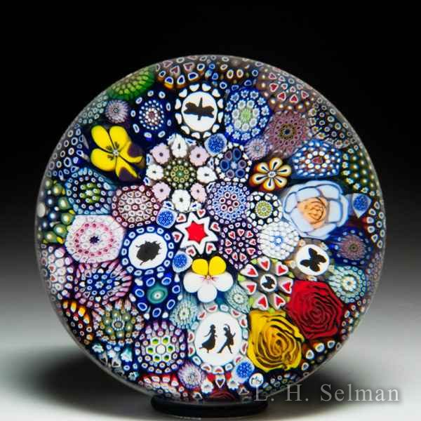 Mike Hunter 2019 close packed millefiori, insect silhouettes, dancing couple silhouette and flower canes paperweight. by Twists Glass Studio