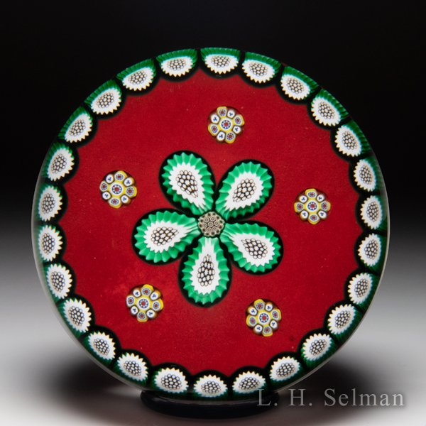 Peter McDougall (2004) Mid-year millefiori daisy and garland on red ground paperweight. by Peter McDougall